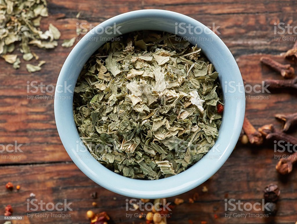 bowl of dried oregano stock photo