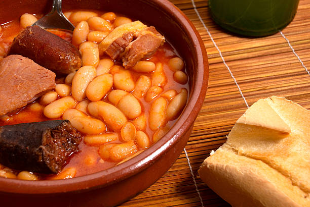 Bowl of fabada on wood placemat with piece of baguette stock photo