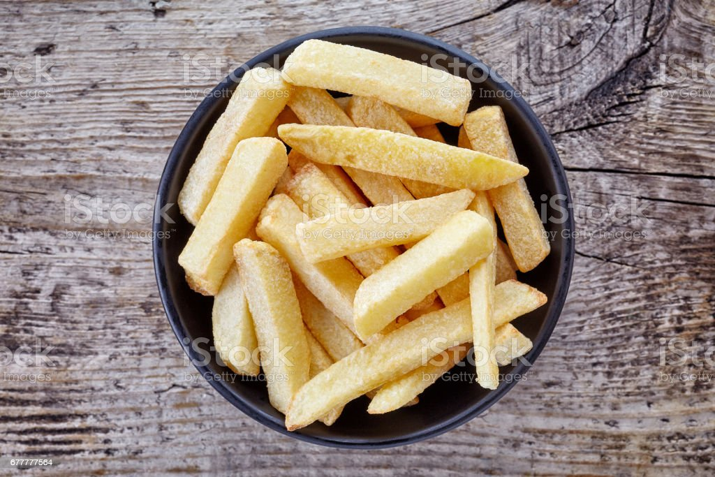Bowl of french fries on wood, from above royalty-free stock photo