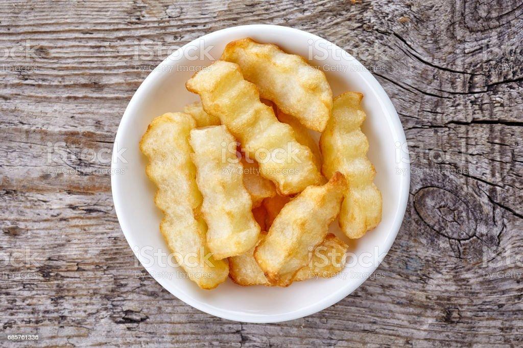Skål med pommes frites på trä, från ovan royaltyfri bildbanksbilder