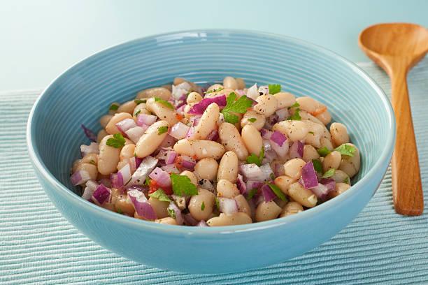 Bowl of fresh bean salad with purple onion stock photo