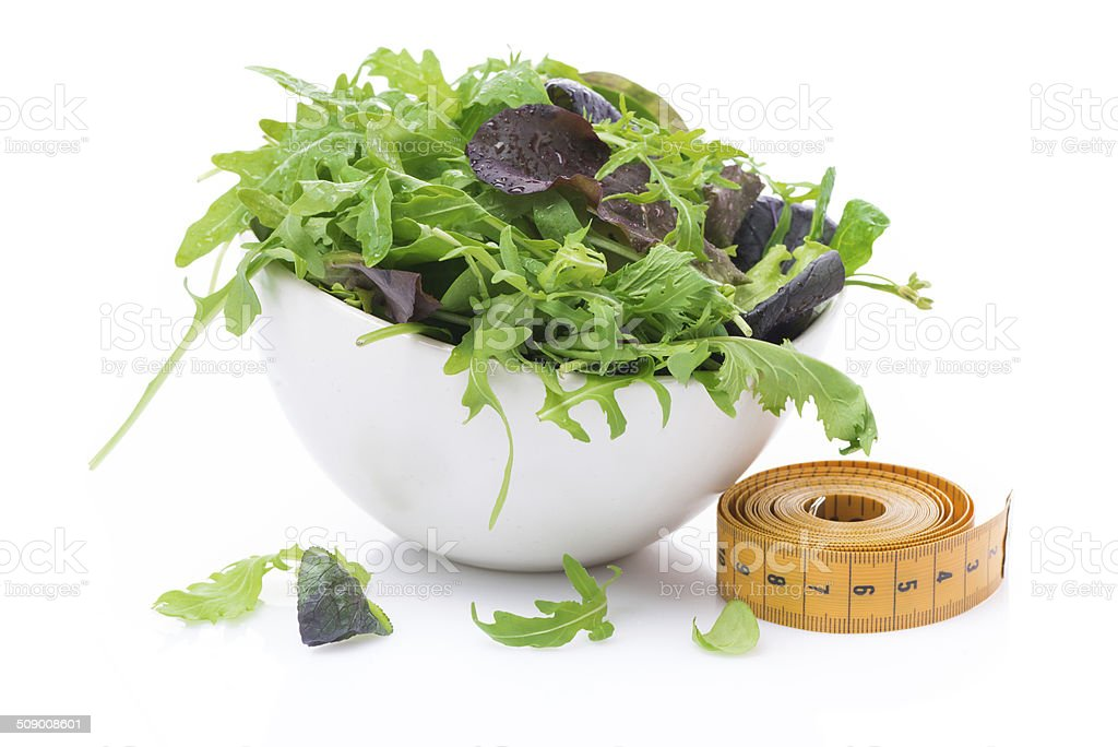 bowl of fresh lettuce and measuring tape, isolated stock photo