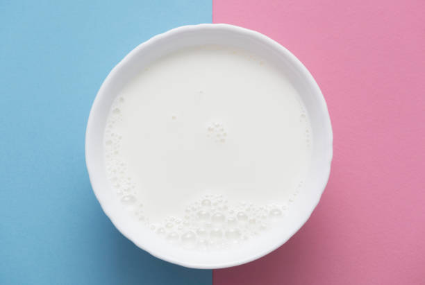 Bowl of fresh milk on rose quartz and serenity blue background. Directly above view. stock photo