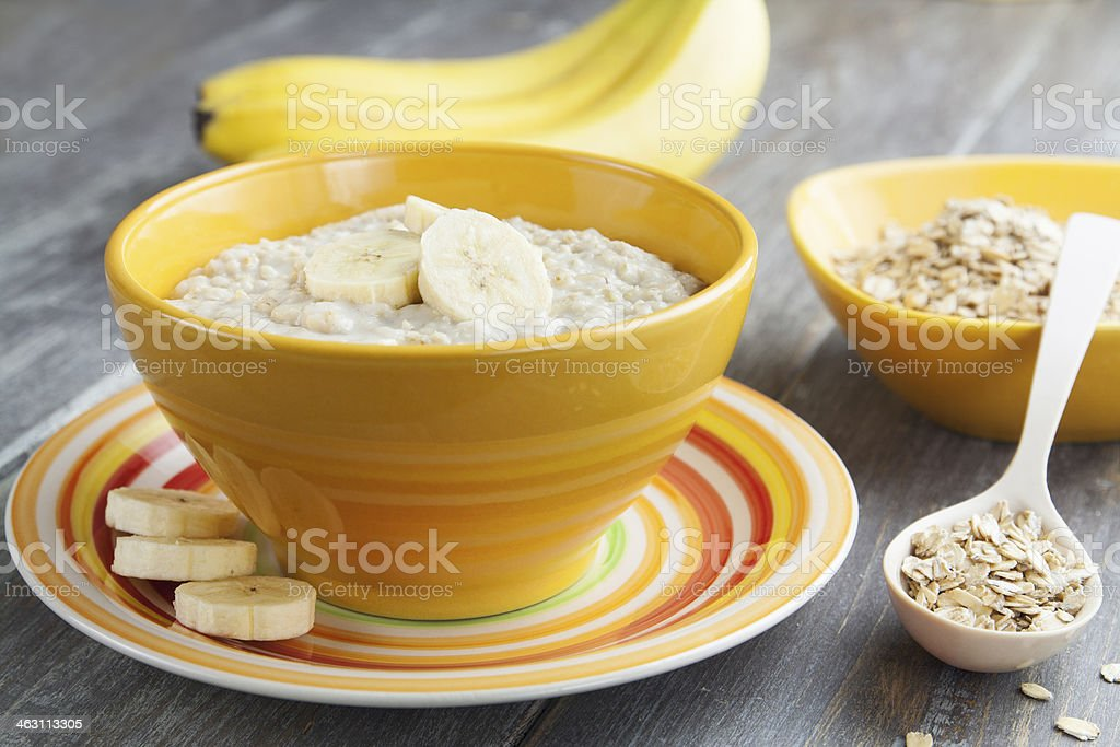 Bowl of fresh oatmeal and bananas with ingredients on side stock photo