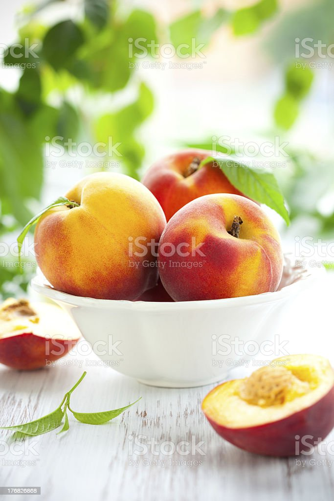 Bowl of fresh peaches on table stock photo