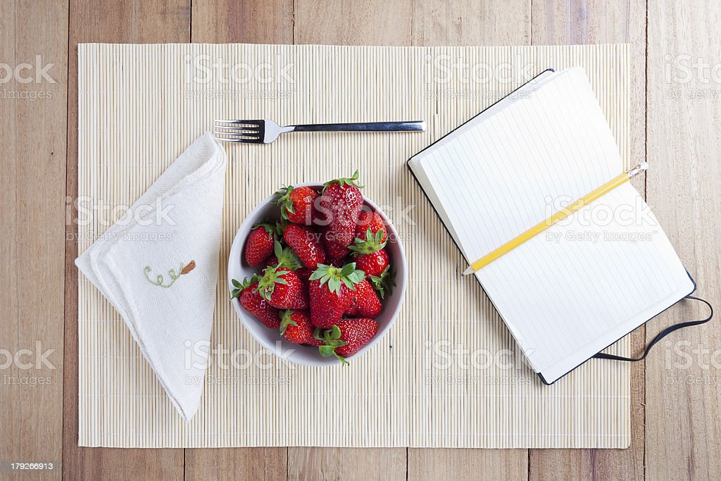 Bowl of fresh strawberries with a notebook royalty-free stock photo