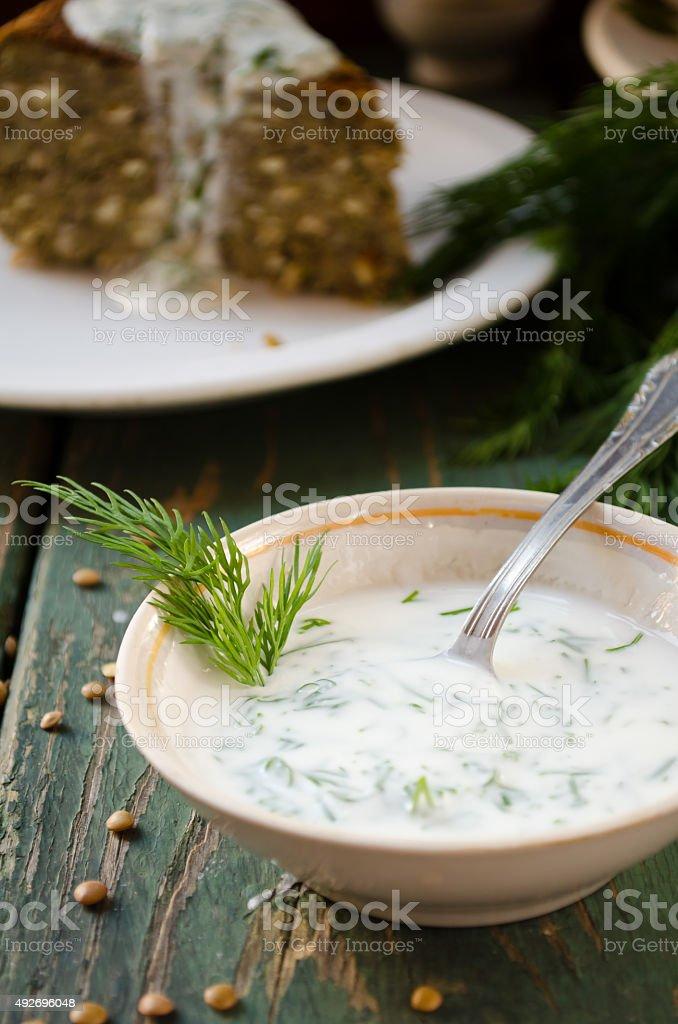 Bowl of fresh yogurt dip with dill and garlic stock photo