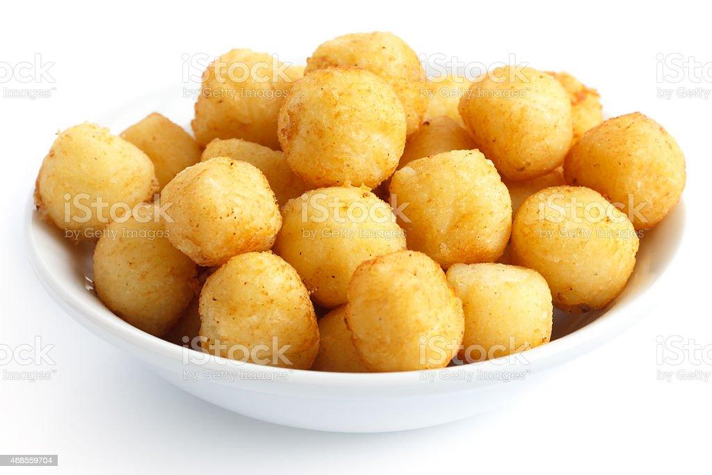 Bowl of fried small potato balls on white. stock photo