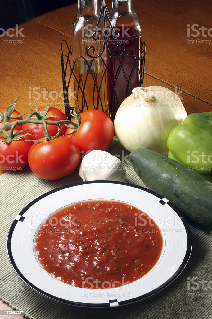 A bowl of gazpacho with vegetables around it royalty-free stock photo