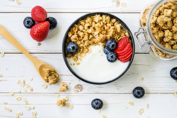 bol de muesli avec yogourt, fruits frais, fraises sur table en bois. - Photo