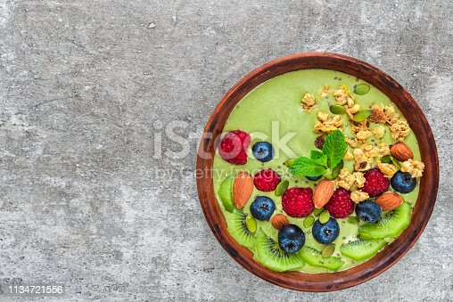 istock bowl of green matcha tea smoothie with fresh berries, fruits, granola, nuts and seeds for healthy vegan breakfast 1134721556
