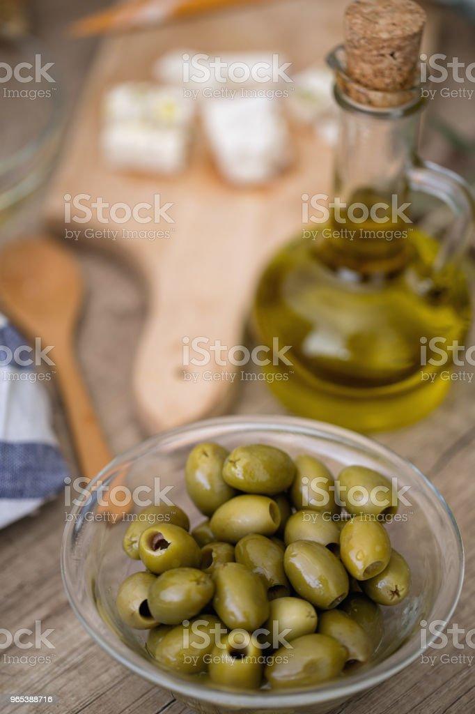 一碗綠色橄欖和一瓶橄欖油在木桌上 - 免版稅健康的生活方式圖庫照片