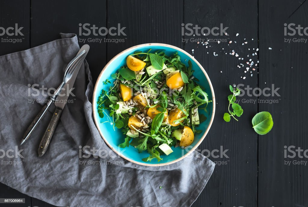 Bowl of green salad with avocado, arugula, cherry tomatoes and sunflower seeds stock photo