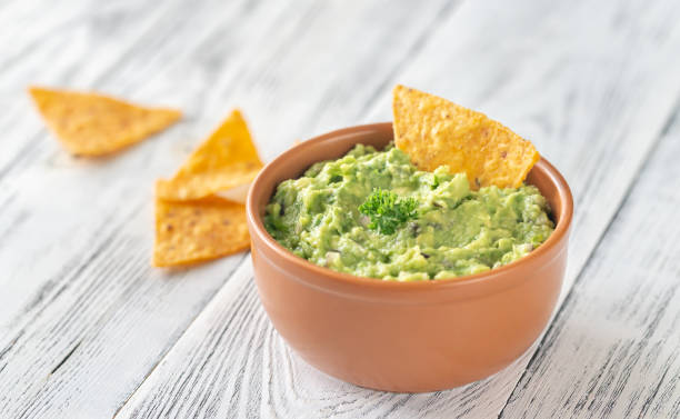 Bowl of guacamole with tortilla chips Bowl of guacamole with tortilla chips close-up dipping sauce stock pictures, royalty-free photos & images