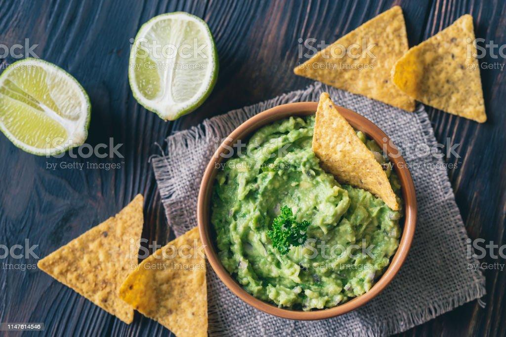 Bowl of guacamole with tortilla chips - Zbiór zdjęć royalty-free (Awokado)
