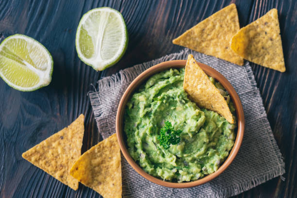 Bowl of guacamole with tortilla chips Bowl of guacamole with tortilla chips: top view dipping sauce stock pictures, royalty-free photos & images