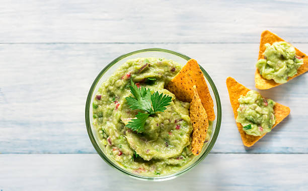 Bowl of guacamole with tortilla chips stock photo
