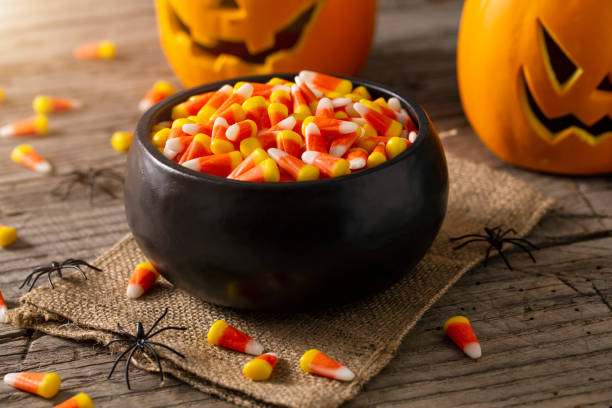 Bowl of Halloween Candy Corns and Jack O' Lantern Bowl of Halloween candy corns with jack o' lanterns and spider decoration on rustic wood table. candy stock pictures, royalty-free photos & images
