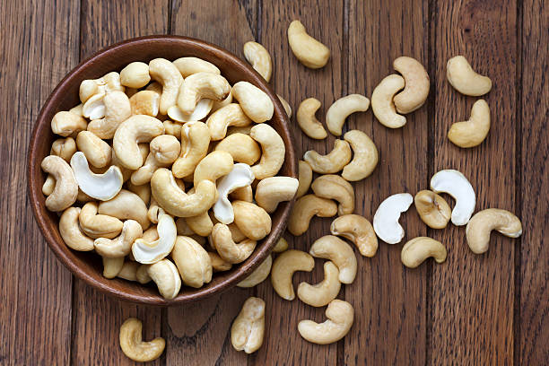 bowl of halved cashew nuts in a wooden bowl - cashew stock photos and pictures