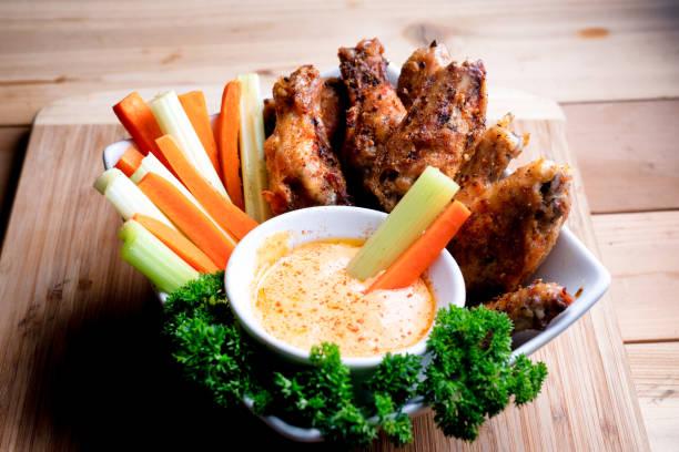 eine schüssel mit gesunden gebackene gegrillte hähnchenflügel begleitet von hot sauce sellerie und karotten-sticks - gewürz für gegrilltes hähnchen stock-fotos und bilder