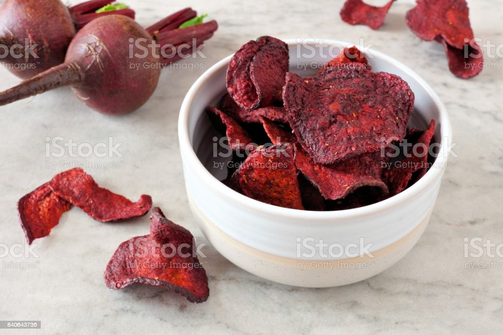 Bowl of healthy beet chips over white marble stock photo