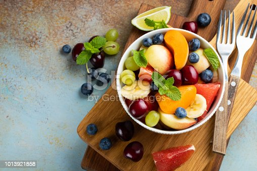 Bowl of healthy fresh fruit salad on a blue rusty background. Top view with copy space. Flat lay.
