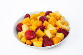 Bowl of healthy fresh fruit salad on white marble background. healthy food. Tropical.