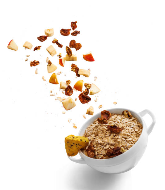 bowl of healthy oatmeal with falling fruit with the ingredients in the air - oats food stock photos and pictures