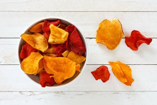 schüssel von gesunden gemüse chips, draufsicht auf weißem holz - gemüsechips stock-fotos und bilder
