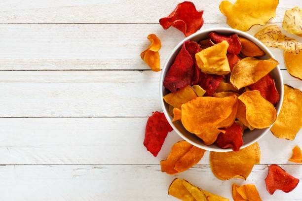 schüssel von gesunden gemüse chips, ansicht von oben mit textfreiraum auf weißem holz - gemüsechips stock-fotos und bilder