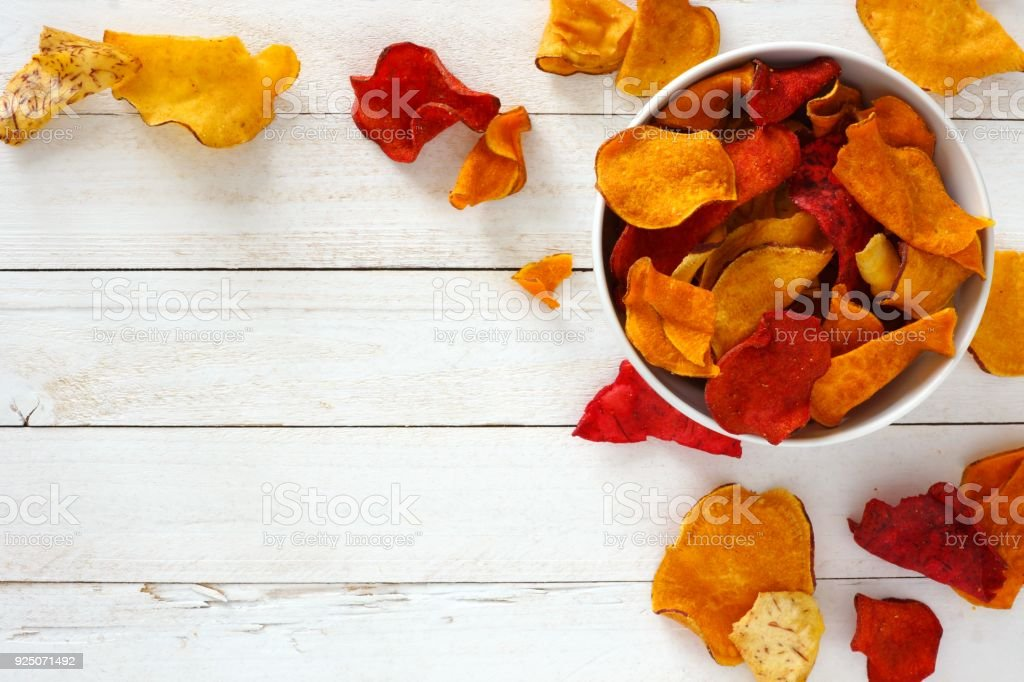 Bowl of healthy vegetable chips, top view with copy space on white wood stock photo