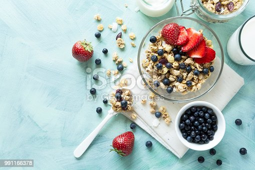 599887760 istock photo Bowl of homemade granola with strawberry, blueberry, milk and yogurt on turquoise wooden background. Top view. Flat lay. Copy space 991166378