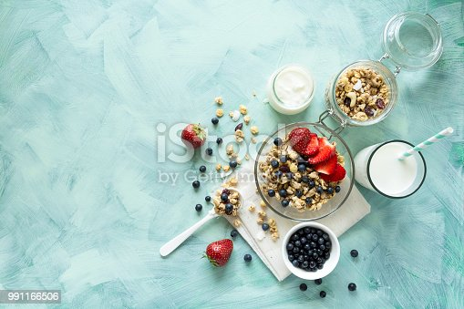 599887760 istock photo Bowl of homemade granola with strawberry, blueberry, milk and yogurt on turquoise wooden background. Top view. Flat lay. Copy space 991166506