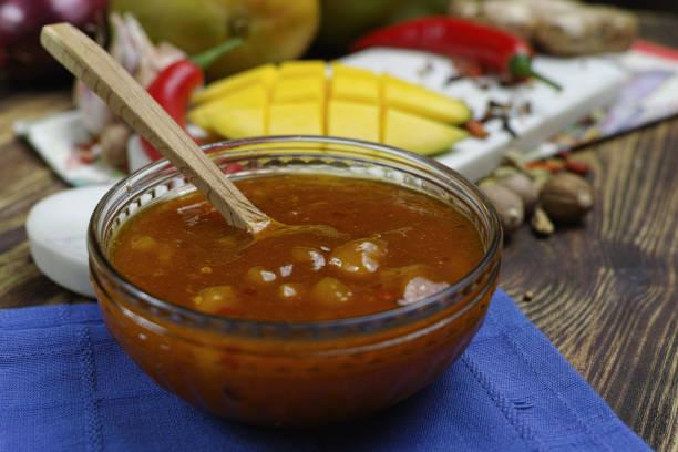 schüssel mit hausgemachtem mango-chutney auf alten holztisch - ingwermarmelade stock-fotos und bilder