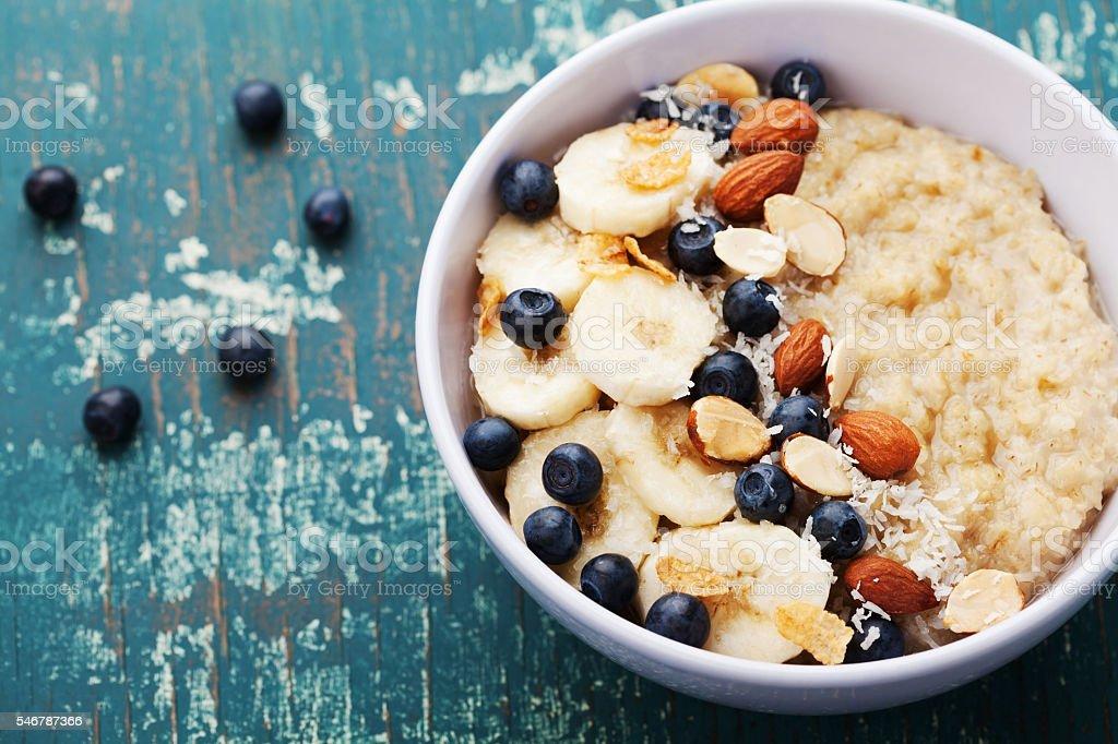 Bowl of homemade oatmeal porridge with banana, blueberries and almonds stock photo