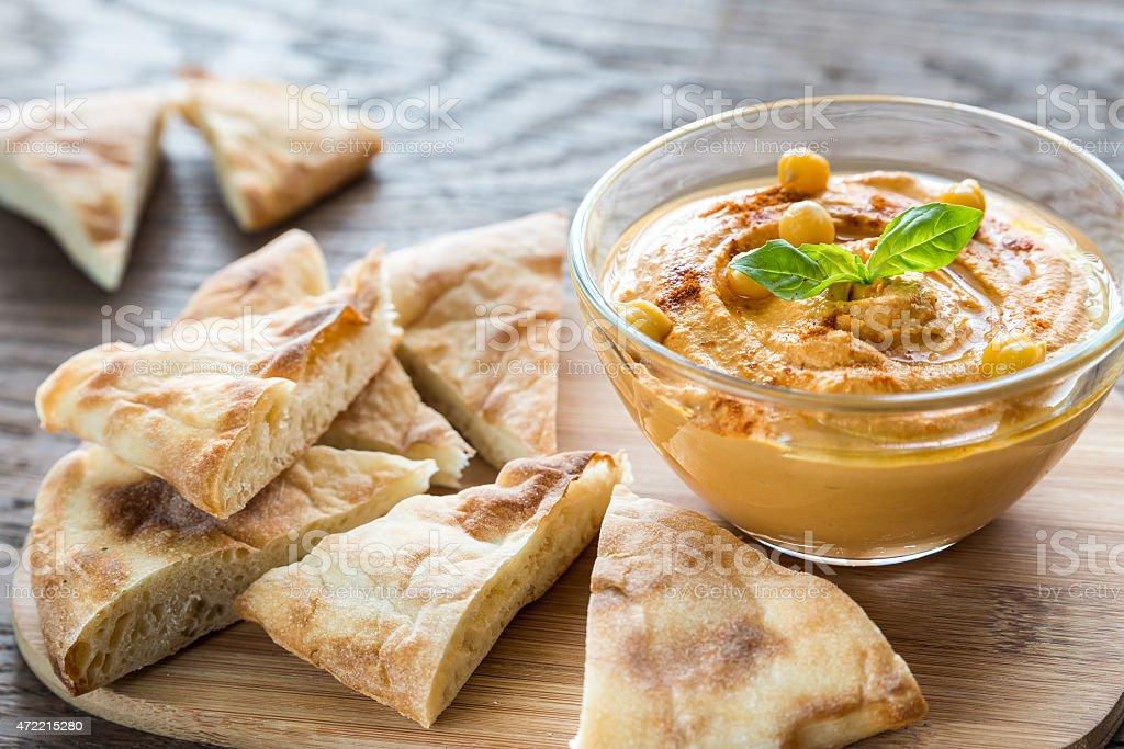 Bowl of hummus with pita slices stock photo