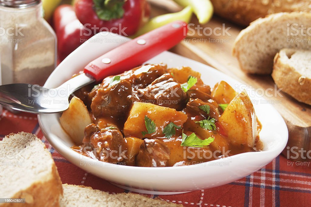 A bowl of Hungarian goulash with a red spoon stock photo