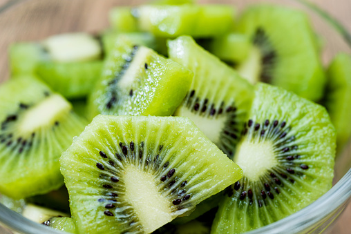 A bowl of kiwi fruit slices on wooden table.