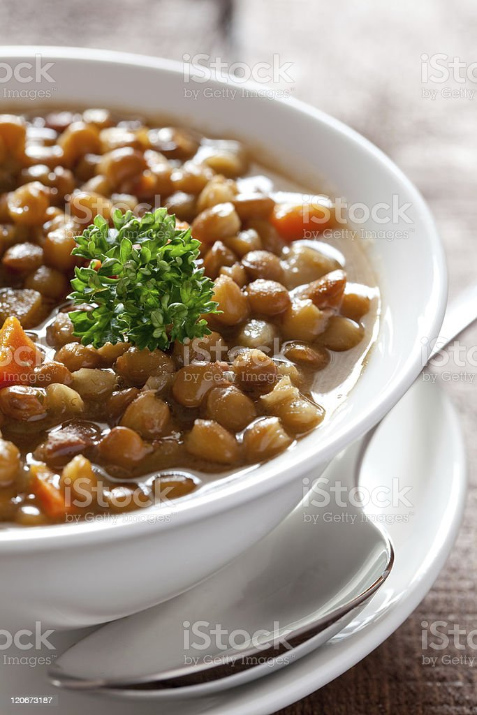 A bowl of lentil soup of a white saucer stock photo