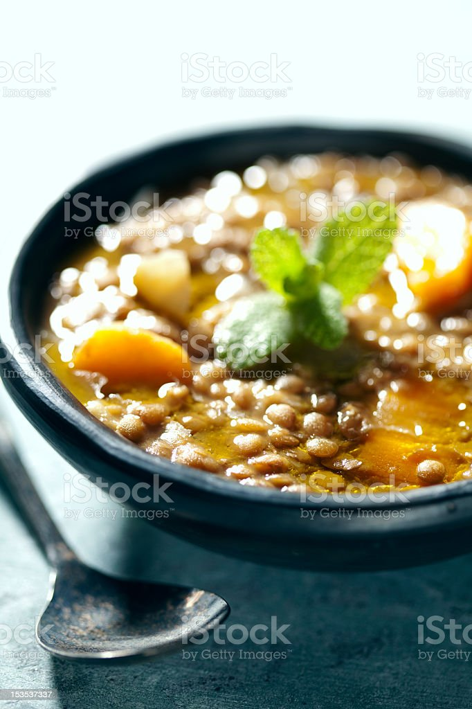 Bowl of lentil soup on table with spoon stock photo