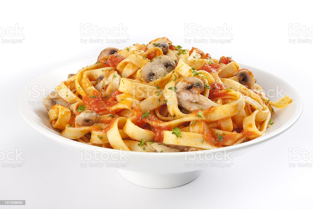 A bowl of linguine with herbs, mushroom and tomato sauce stock photo