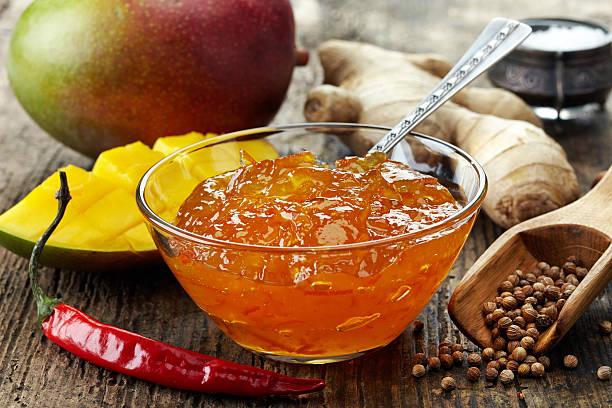 schüssel mit mango-chutney auf holztisch - ingwermarmelade stock-fotos und bilder