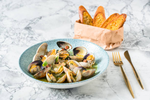 Bowl of Manila Clams Freshly steamed Manila Clams dish with white wine,chili pepper and parsley mollusk stock pictures, royalty-free photos & images