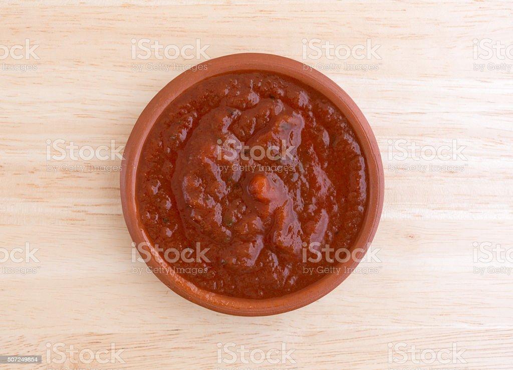 Bowl of marinara sauce on a wood table top stock photo