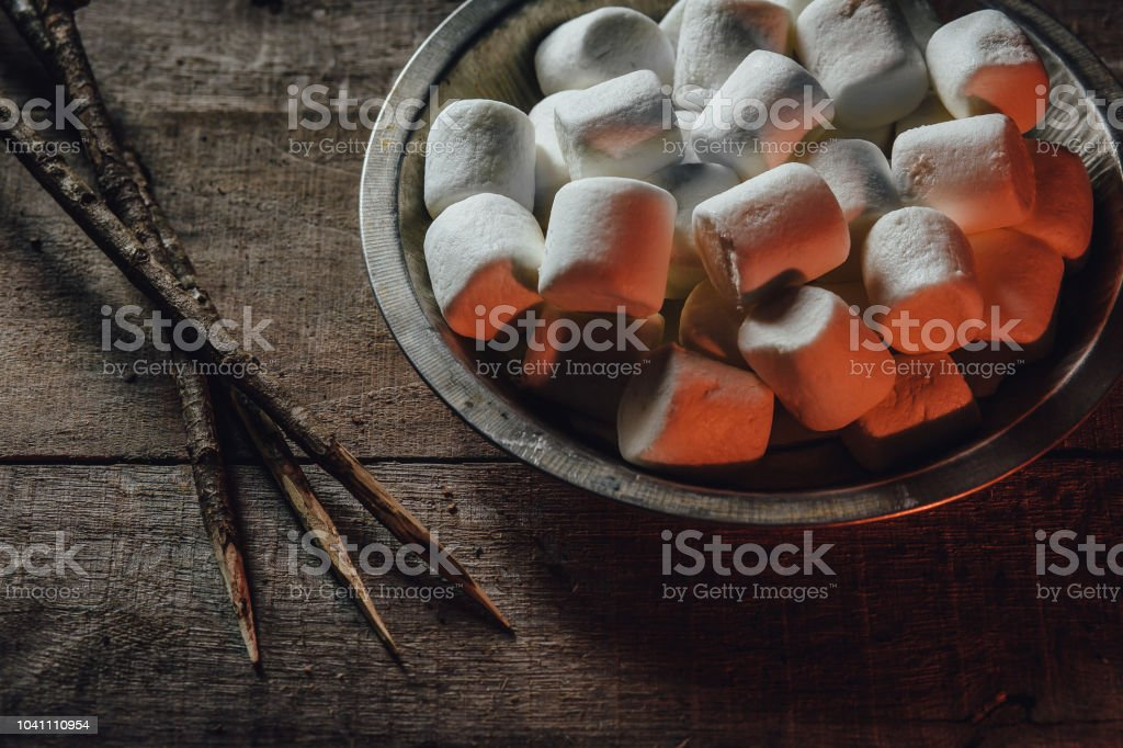 Bowl of marshmallows and skewers by fire light stock photo