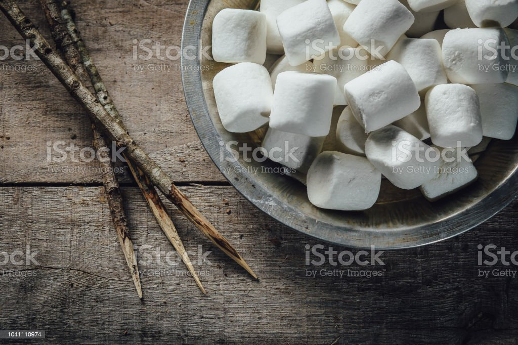 Bowl of marshmallows and skewers stock photo
