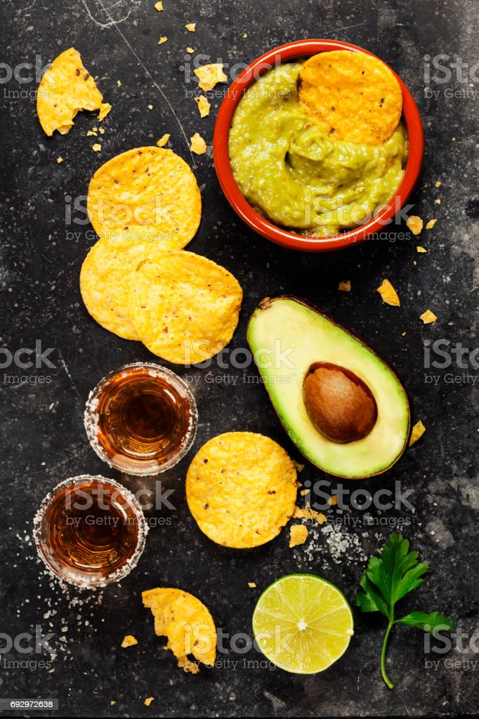 Bowl of mexican nachos chips with homemade fresh guacomole sauce and tequila shots stock photo