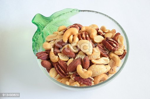 A bowl of mildly salted mixed nuts is hailed as a healthy and nutritious alternative  to unhealthy choices like biscuits, chips, sugary sodas, chocolates and other similar hugh sugar foods. Bowl isolated against plain white background.