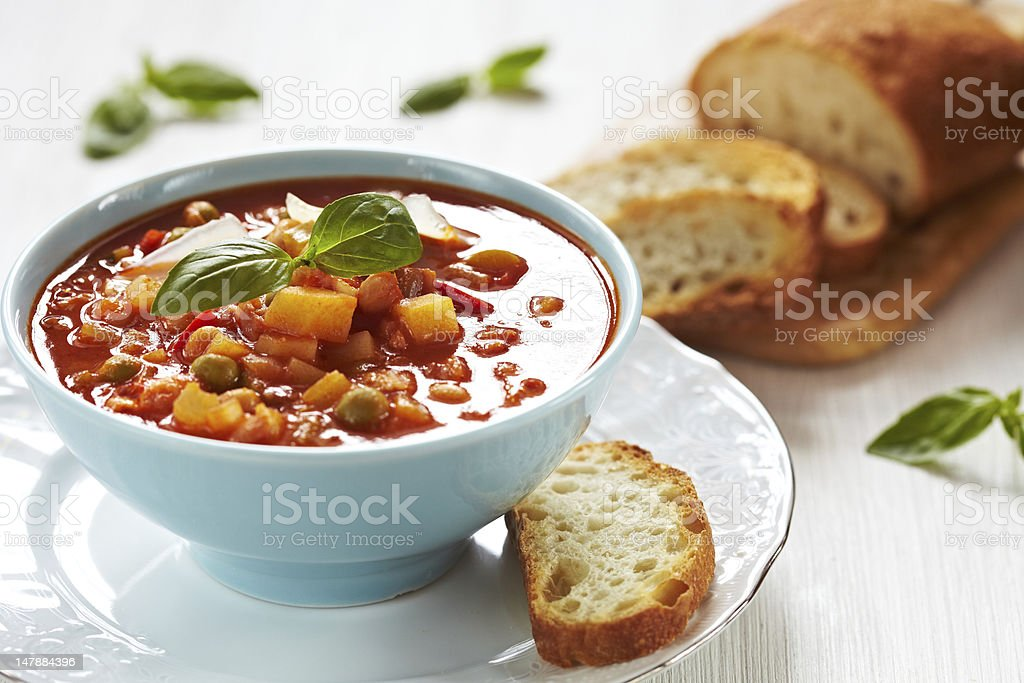 Bowl of minestrone soup with a slice of bread on the side royalty-free stock photo