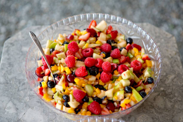Bowl of Mixed Fruit Round glass blow with fruit salad and a spoon fruit salad stock pictures, royalty-free photos & images